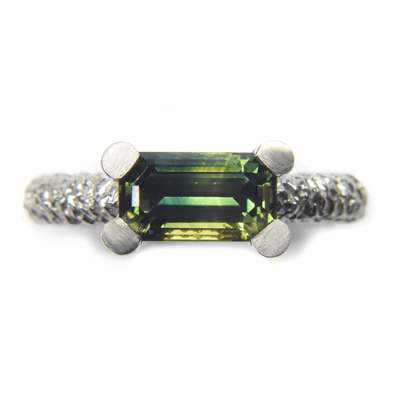emerald cut green sapphire engagement ring in partially eroded 18ct white gold